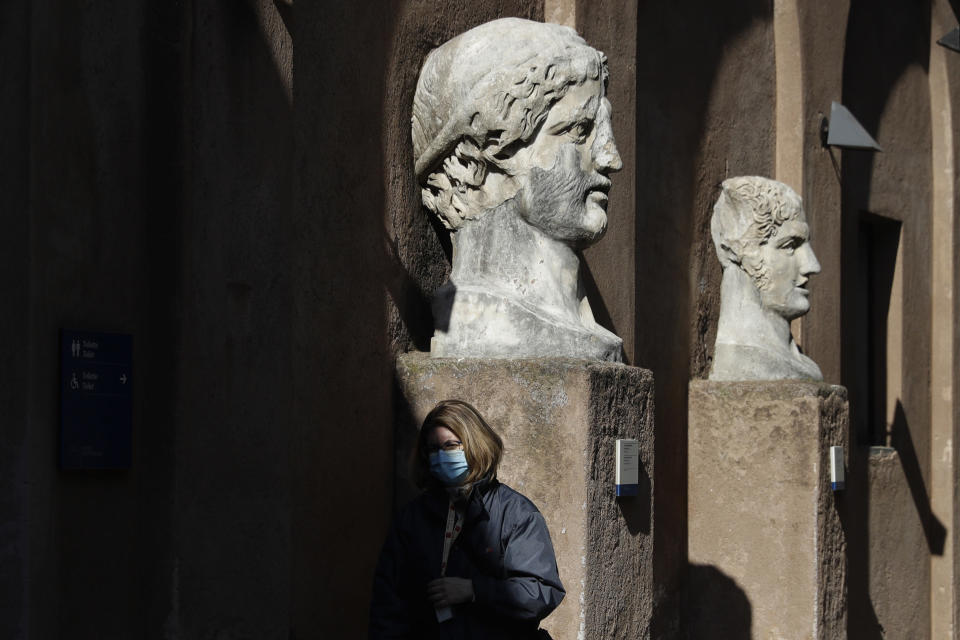 A museum usher stands by marble busts at the entrance of the Sant'Angelo castle In Rome Tuesday, March 2, 2021. The first anti-pandemic decree from Italy's new premier, Mario Draghi, tightens measures governing school attendance while easing restrictions on museums, theaters and cinemas. Italy, a nation of 60 million people where COVID-19 first erupted in the West in February 2020, has registered nearly 3 million confirmed cases. Its known death toll of more than 98,000,is the second-highest in Europe, after Britain's. (AP Photo/Gregorio Borgia)