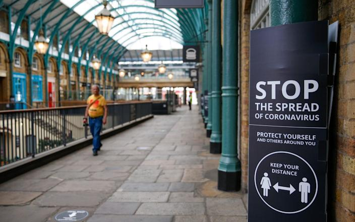 A coronavirus sign stands on a post in the Covent Garden district of London - Hollie Adams/Bloomberg