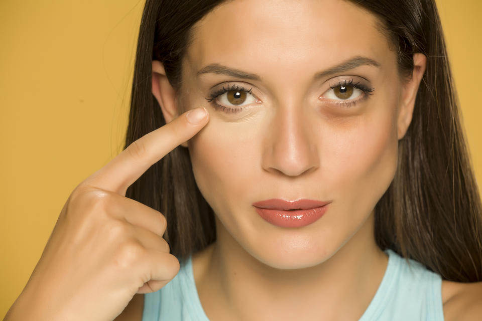 Young woman applying concealer on her  low eyelids on yellow background