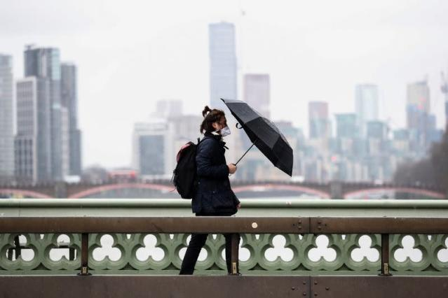 A man wearing a protective mask walks across Westminster Bridge with an umbrella in London Britain