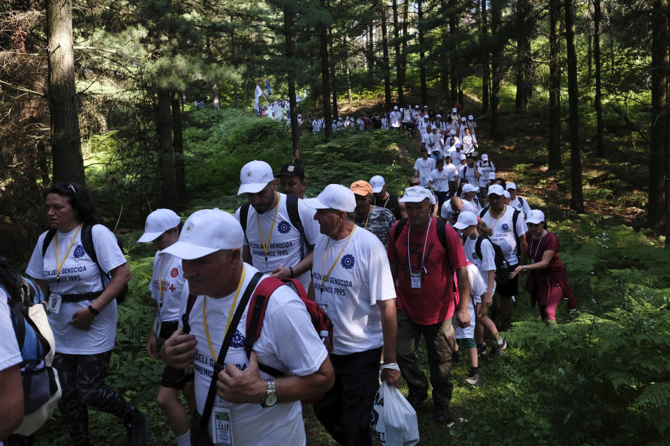 FILE - In this July 8, 2021, file photo, participants, some of them survivors of the 1995 Srebrenica massacre, walk through a mountain area near Nezuk, Bosnia, during a Peace March recreating the path taken 26 years ago by people trying to escape the advancing Bosnian Serb forces. Twenty-six years after the July 1995 Srebrenica massacre, the only episode of Bosnia's 1992-95 war to be legally defined as genocide, its survivors continue to grapple with the horrors they endured while also confronting increasingly aggressive downplaying and even denial of their ordeal. (AP Photo/Kemal Softic, File)