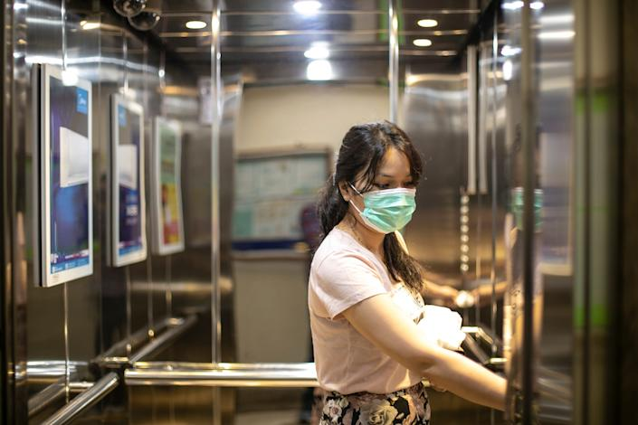 A young woman in an elevator wears a face mask to prevent coronavirus spread.