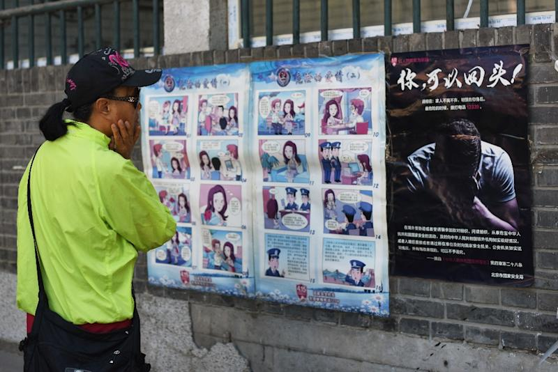 A woman looks at a propaganda cartoon warning local residents about foreign spies, in an alley in Beijing on May 23, 2017