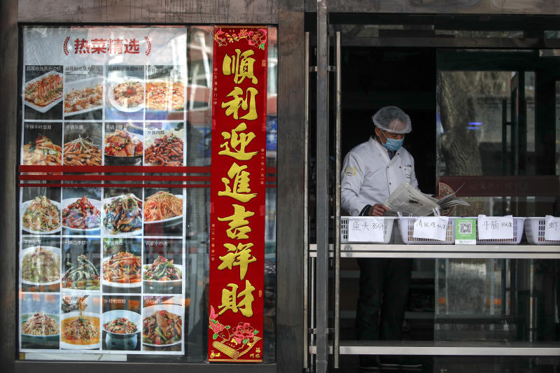 An employee wearing protective gear reads a newspaper at a restaurant only offering take-out orders following the coronavirus outbreak in Beijing, Sunday, March 1, 2020. Amid fears about where the next outbreak of a fast-spreading new virus would appear, infections and deaths continued to rise across the globe Sunday, emptying streets of tourists and workers, shaking economies and rewriting the realities of daily life. (AP Photo/Andy Wong)