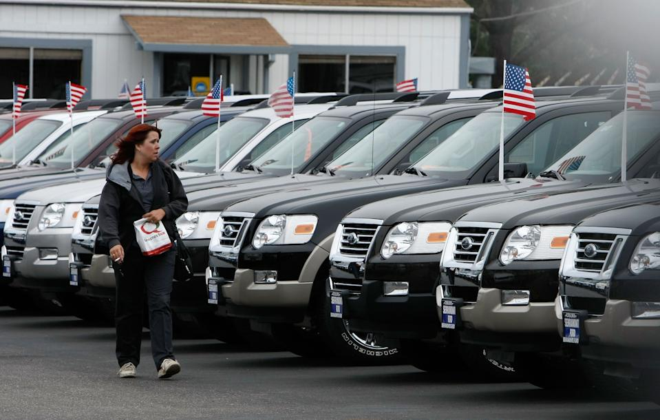 A woman looks at a row of new Ford trucks at a Ford dealership in Colma, California. (Photo: Justin Sullivan/Getty Images)
