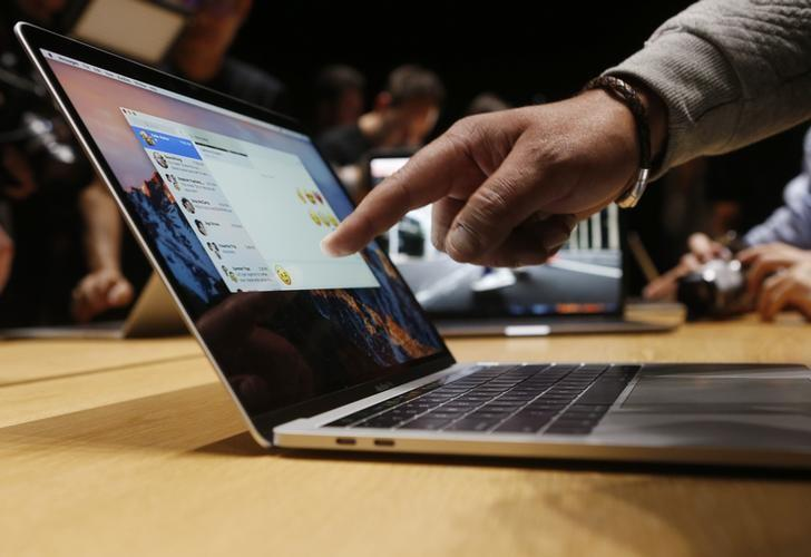 FILE PHOTO - A guest points to a new MacBook Pro during an Apple media event in Cupertino