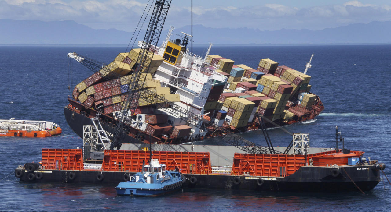 FILE - In this Nov. 14, 2011 file image released by New Zealand Maritime, a sea crane, foreground, is in place to begin removing some of the 1,280 containers that remain on board the cargo ship Rena, near Tauranga, New Zealand. Australian inspection records show that a cargo ship that ran aground off New Zealand in October had previous safety issues. (AP Photo/New Zealand Maritime, Graeme Brown, File) EDITORIAL USE ONLY