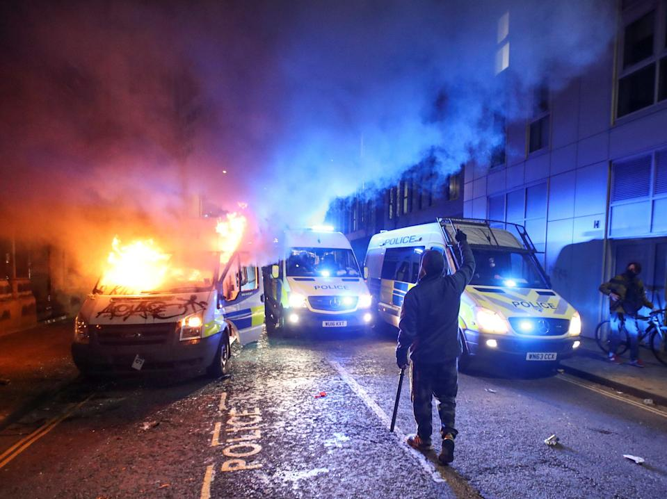 A demonstrator gestures near a burning police van during a protest against a new proposed policing bill in Bristol (Peter Cziborra/Reuters)