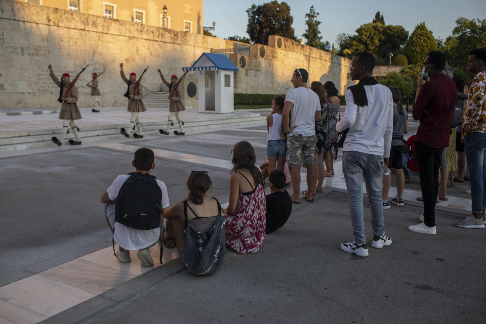 Tourists look at the changing of presidential guards ceremony outside the Greek parliament , in Athens, on Friday, July 31, 2020. Greek authorities introduced tougher restrictions this week following an increase in infections, most unrelated to tourism. (AP Photo/Petros Giannakouris)