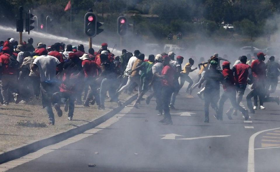 Members of the Economic Freedom Fighters (EFF) flee from teargas, stun grenades and water canons fired by police during a protest near the Brackenfell High school in Cape Town, South Africa, Friday, Nov. 20, 2020. (AP Photo/Nardus Engelbrecht)