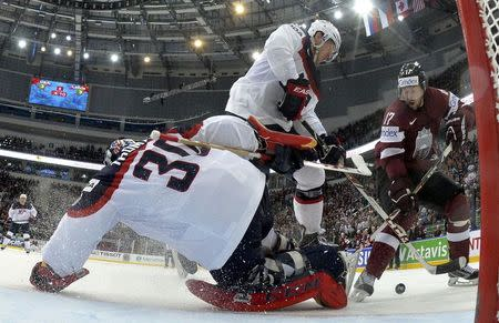 Goalie Tim Thomas and Matt Donovan of the U.S. are challenged by Latvia's Aleksandrs Nizivijs (L-R) during their men's ice hockey World Championship Group B game at Minsk Arena in Minsk May 15, 2014. REUTERS/Alex Kudenko/Pool