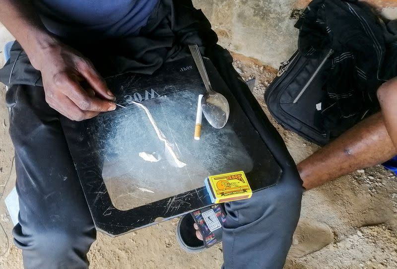 """Man shows a substance known as """"bombe"""", a mix of catalytic converters' crushed honeycomb and pills, in Kinshasa"""
