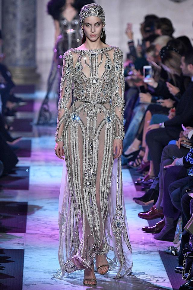 <p>Model wears a semi-sheer crystal and sequin-embroidered dress with matching headpiece from the Elie Saab SS18 Haute Couture show. (Photo: Getty Images) </p>