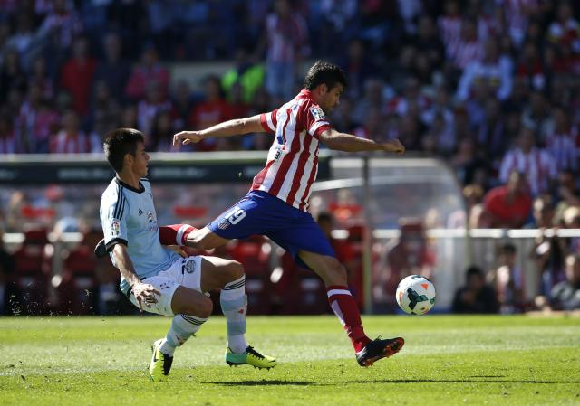 Atletico Madrid's Diego Costa (R) controls the ball past Celta Vigo's David Costas to score during their Spanish first division soccer match at Vicente Calderon stadium in Madrid October 6, 2013. REUTERS/Susana Vera (SPAIN - Tags: SPORT SOCCER)