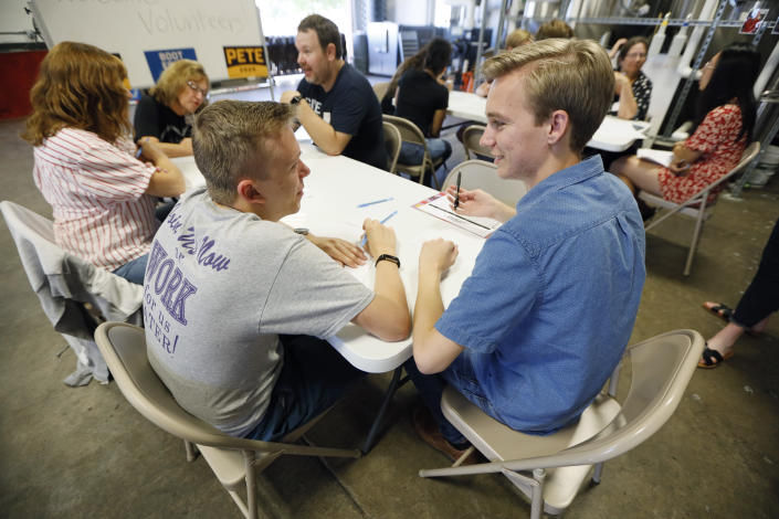 """Kyle Rittmueller, left, and Michael Paulson, right, supporters of Democratic presidential candidate Pete Buttigieg, participate in a """"relational phone bank"""" at a local brewery, Thursday, Aug. 29, 2019, in West Des Moines, Iowa. The two Drake University students were part of a group that worked their smartphones calling and texting friends to test their interest the candidate. Buttigieg is well behind his better known rivals in Iowa who have spent months building a deep organizational structure in the state that marks the first test for the Democratic presidential nomination. But thanks to his campaign taking in nearly $25 million in contributions in the last quarter, money that he is using to help create an army of peer-to-peer foot soldiers, Buttigieg is rapidly trying to catch up. (AP Photo/Charlie Neibergall)"""