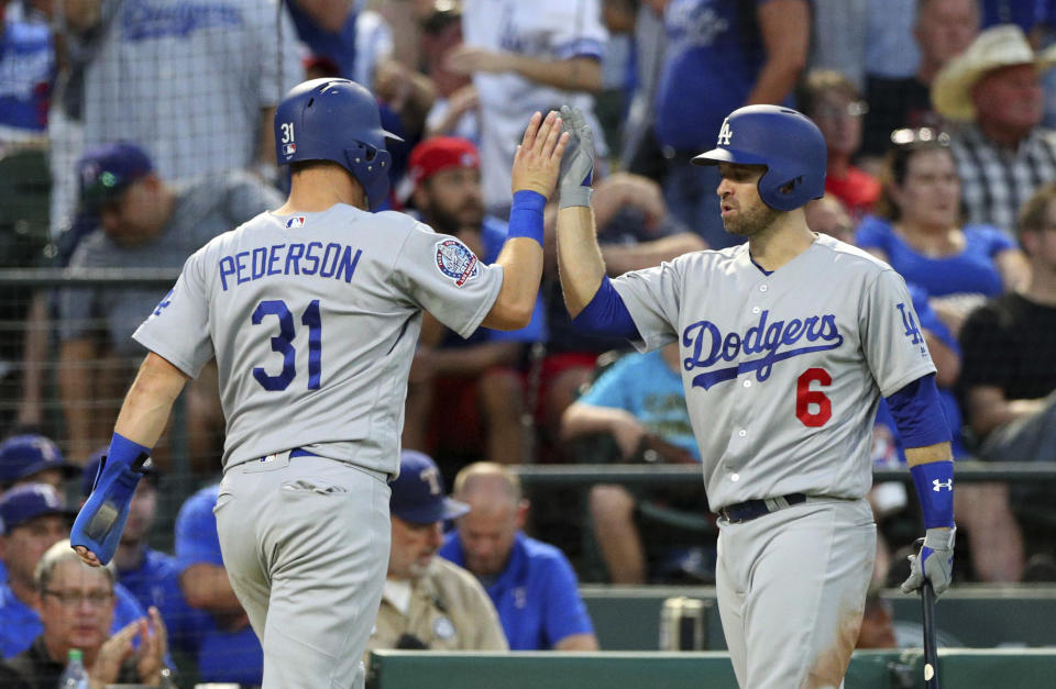 Los Angeles Dodgers' Joc Pederson (L) high fives Brian Dozier after scoring against the Texas Rangers in the third inning of a baseball game Tuesday, Aug. 28, 2018, in Arlington, Texas. (AP Photo)