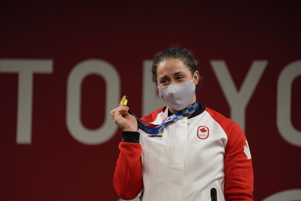 Maude G. Charron of Canada cries as she celebrates her gold medal on the podium of the women's 64kg weightlifting event, at the 2020 Summer Olympics, Tuesday, July 27, 2021, in Tokyo, Japan. (AP Photo/Luca Bruno)