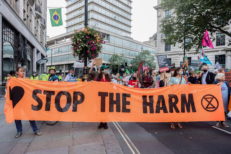 LONDON, UNITED KINGDOM - 2021/08/25: Protesters hold a banner expressing their opinions during the demonstration. On the 3rd day of Extinction Rebellion's protests, protesters came together with the aim of demanding climate justice for the Indigenous people of Amazon rainforests in Brazil. They protest against ecocide and deforestation in Brazil. The group began their demonstration outside Brazilian Embassy in London, then moved over to Piccadilly Circus, and lastly occupying Oxford Circus. (Photo by Belinda Jiao/SOPA Images/LightRocket via Getty Images)