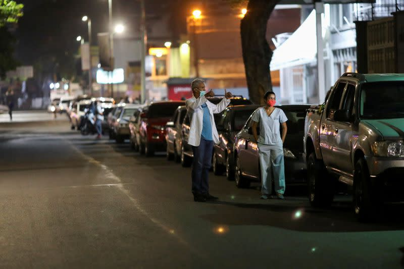 FILE PHOTO: Doctors Carlos Martinez and Maria Martinez wait in line to get fuel at a gas station, during a nationwide quarantine due to the coronavirus disease (COVID-19) outbreak, in Caracas