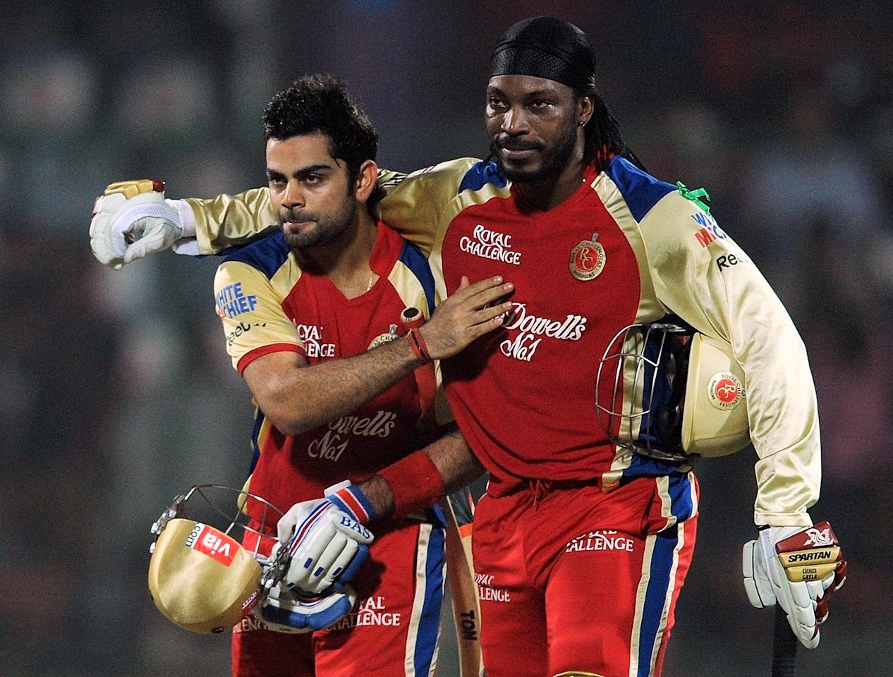 Royal Challengers Bangalore batsman Chris Gayle (R) hugs teammate Virat Kohli after the end of their innings during the IPL Twenty20 cricket match between Delhi Daredevils and Royal Challengers Bangalore at the Feroz Shah Kotla stadium in New Delhi on May 17, 2012.      RESTRICTED TO EDITORIAL USE. MOBILE USE WITHIN NEWS PACKAGE. AFP PHOTO/ MANAN VATSYAYANA          (Photo credit should read MANAN VATSYAYANA/AFP/GettyImages)