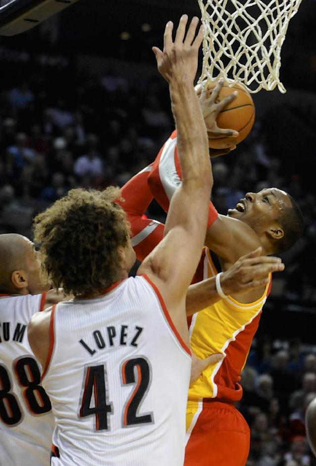 Houston Rockets' Dwight Howard, right, shoots against Portland Trail Blazers' Robin Lopez (42) and Nicolas Batum (88) during the first half of an NBA basketball game in Portland, Ore., Thursday Dec. 12, 2013. (AP Photo/Greg Wahl-Stephens)