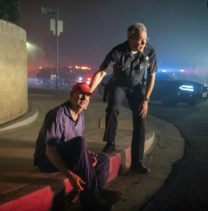 Los Angeles Police Department Chief Michel Moore tells resident Jerry Rowe that firefighters are coming after the roof of Rowe's home caught fire from the Saddleridge fire in Granada Hills, Calif., Friday, Oct. 11, 2019. (AP Photo/Michael Owen Baker)