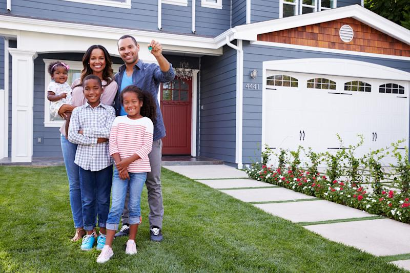 family of five standing in front of home with dad holding up keys