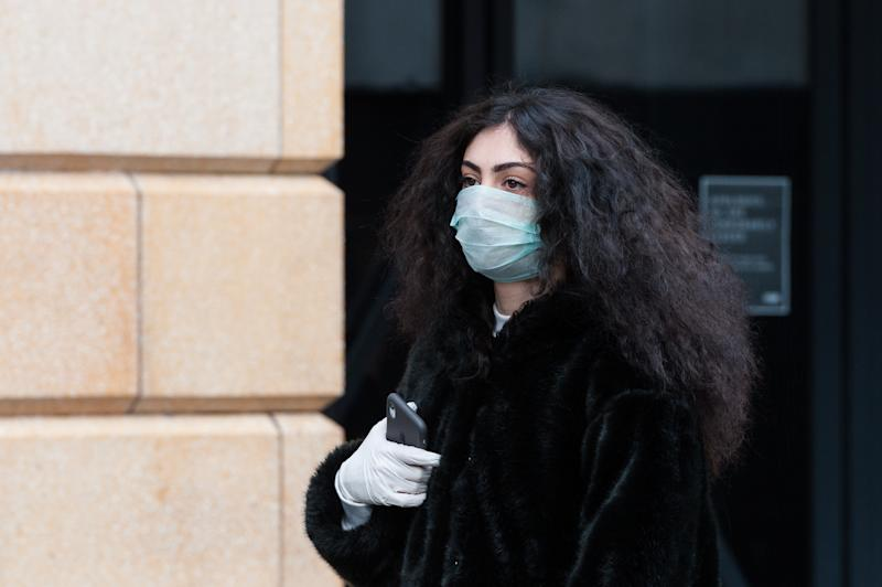 A young woman wears a protective face mask walks in Leicester Square in central London as the coronavirus pandemic continues.