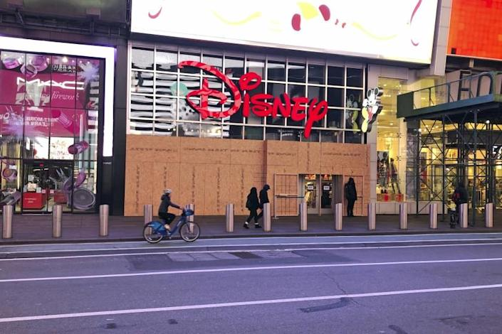 A Disney Store in Times Square is open to customers but remains boarded up after fears of presidential election turbulence in New York on Tuesday, November 17, 2020. (AP Photo/Ted Shaffrey)