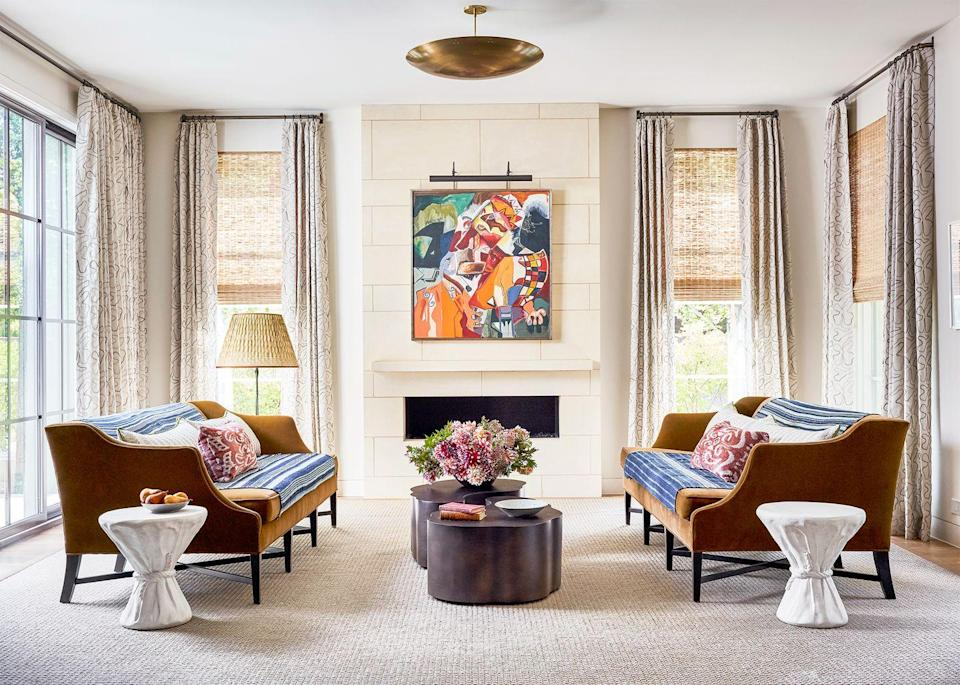 """<p>Warmer than white but still neutral, cream is the perfect background for an inviting yet formal living room. In this one designed by <a href=""""https://www.jeanliudesign.com/"""" rel=""""nofollow noopener"""" target=""""_blank"""" data-ylk=""""slk:Jean Liu"""" class=""""link rapid-noclick-resp"""">Jean Liu</a>, the neutral, almost iridescent rug, velvet sofa, and brass accents are emboldened by the paint color while the blue throw and white side table contrast with it nicely.</p>"""