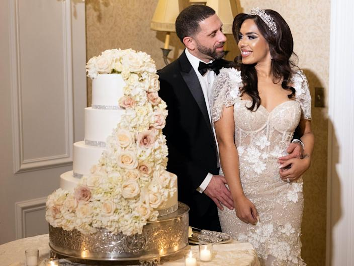 Vishnell and her husband pose next to their wedding cake
