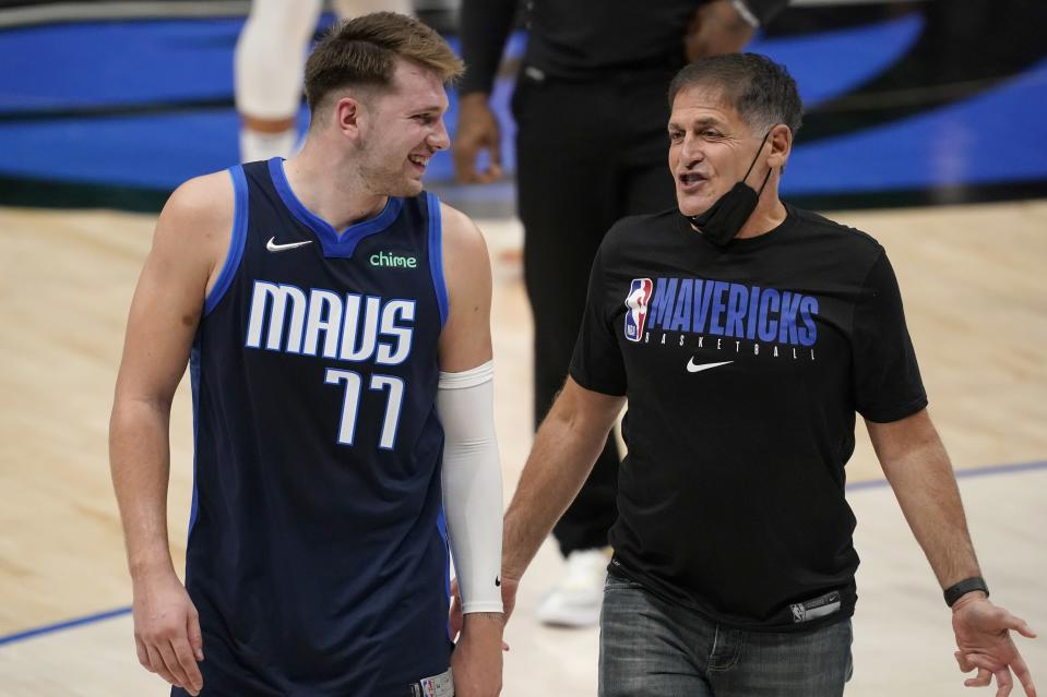 Dallas Mavericks guard Luka Doncic (77) smiles as he talks with team owner Mark Cuban as they walk off the court after the team's win in an NBA basketball game against the Detroit Pistons in Dallas, Wednesday, April 21, 2021. (AP Photo/Tony Gutierrez)