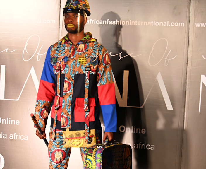 A male model donning a colourful helmet and suitcase takes part in a fashion show in Johannesburg, South Africa - Tuesday 25 May 2021