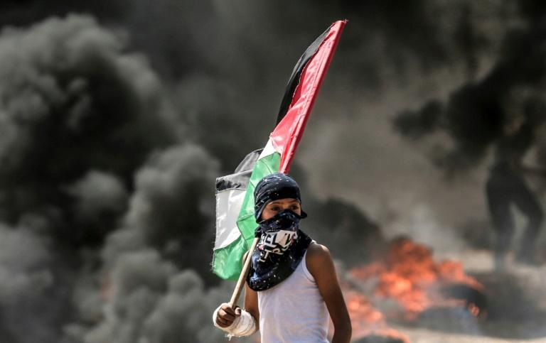 A Palestinian boy holds a flag during protests near the border between the Gaza Strip and Israel on May 14, 2018