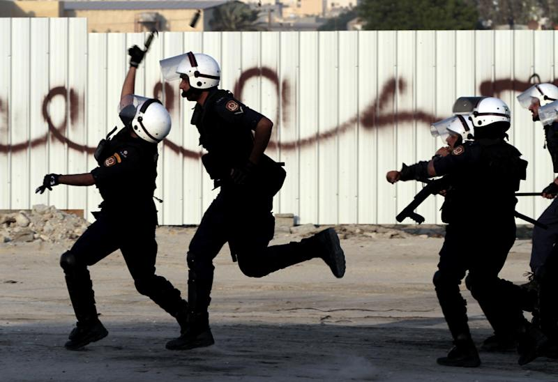 Riot police throw stun grenades and fire tear gas as they run after Bahraini anti-government protesters during clashes with riot police in Sadad, Bahrain, on Saturday, Sept. 29, 2012, after the politically charged funeral for Ali Hussein Niema, 17, who allegedly was shot dead by riot police late Friday. The death could bring fresh protests by Shiite-led groups seeking a greater political voice in the Sunni-ruled Gulf kingdom. (AP Photo/Hasan Jamali)