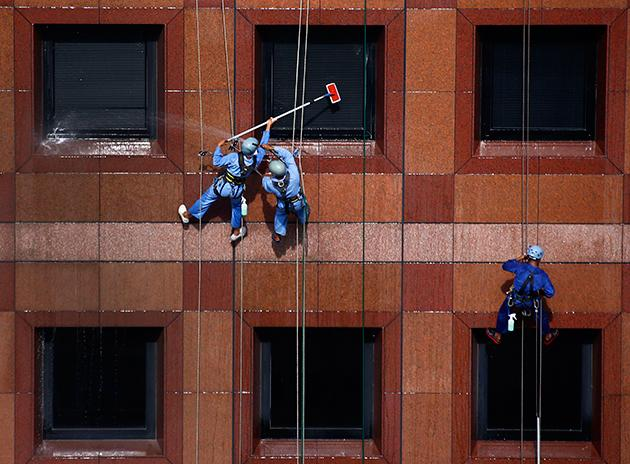 Window cleaners hang from the facade of Ngee Ann city mall in Singapore January 9, 2014. (Reuters/Petar Kujundzic)