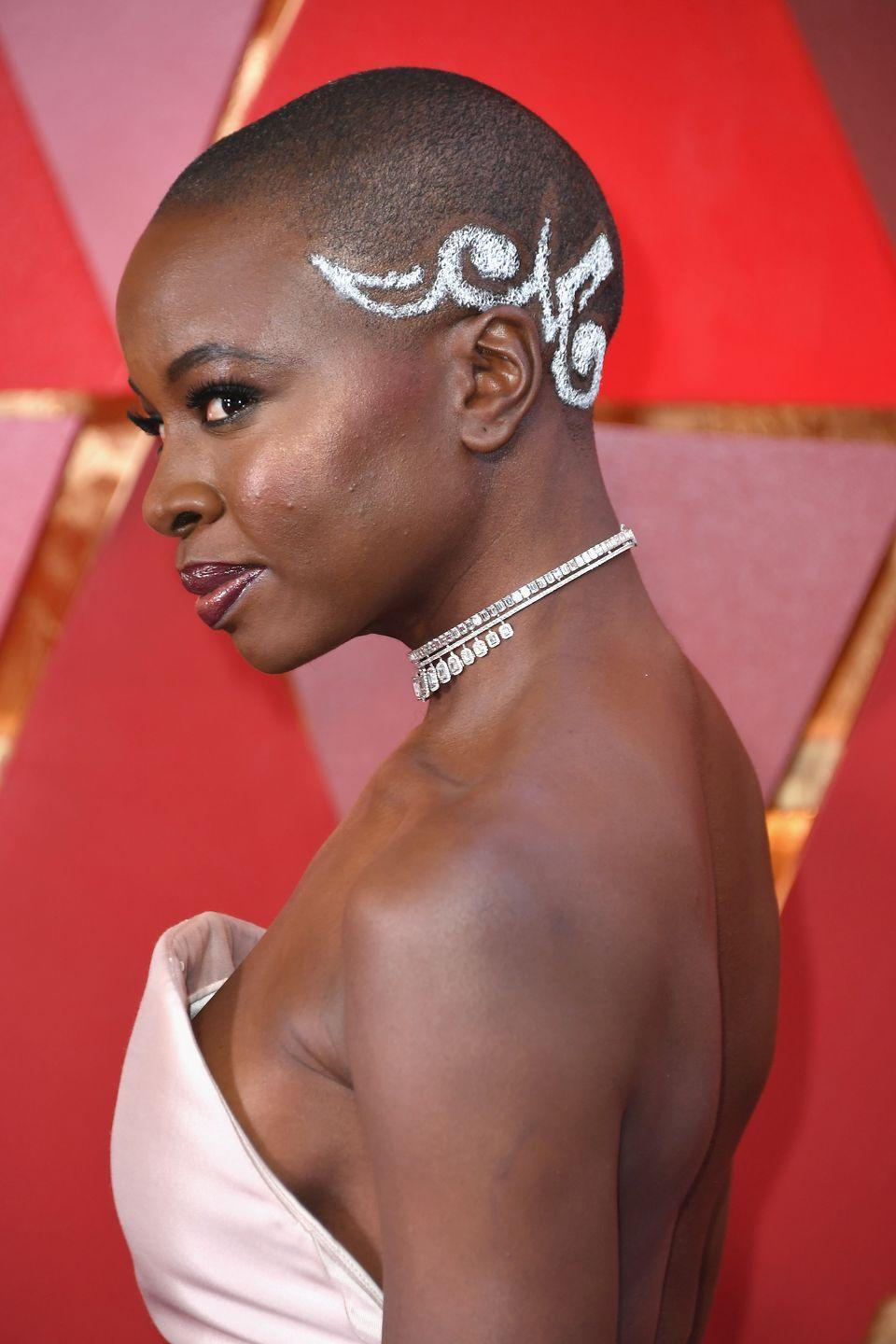 """<p>Take your barber cut look up several notches like actress <strong>Danai Gurira</strong>. Not only did she have an intricate design, she added some sparkle for the Academy Awards. (At home, you can mimic this look using <a href=""""https://go.redirectingat.com?id=74968X1596630&url=https%3A%2F%2Fwww.walmart.com%2Fip%2FTRESemm-Colored-Hair-Spray-Silver-1-8-oz%2F794864662&sref=https%3A%2F%2Fwww.goodhousekeeping.com%2Fbeauty%2Fhair%2Fg2471%2Fshort-black-hairstyles-ideas%2F"""" rel=""""nofollow noopener"""" target=""""_blank"""" data-ylk=""""slk:TRESemmé Glitter Hair Spray in Silver"""" class=""""link rapid-noclick-resp"""">TRESemmé Glitter Hair Spray in Silver</a>.) Ensure you keep the stencil in place and cover the rest of your head so the spray just fills in the design. </p>"""