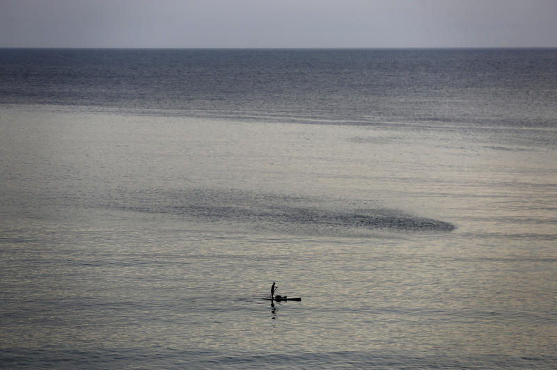 A man stands on his surf on Beirut's Mediterranean Sea, as he back to the beach an hour before the starting of the nighttime curfew that imposed by the government to help stem the spread of the coronavirus, in Beirut, Lebanon, Saturday, April 4, 2020. The virus causes mild or moderate symptoms for most people, but for some, especially older adults and people with existing health problems, it can cause more severe illness or death. (AP Photo/Hussein Malla)