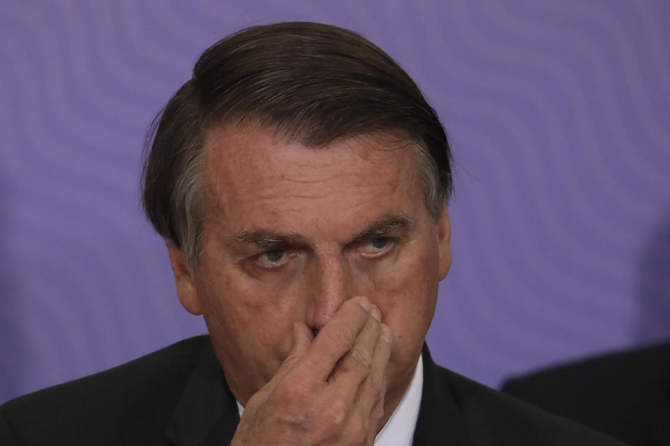 Brazilan President Jair Bolsonaro touches his nose during a ceremony presenting his nation's National Vaccination Plan Against COVID-19 at Planalto presidential palace in Brasilia, Brazil, Wednesday, Dec. 16, 2020. (AP Photo/Eraldo Peres)
