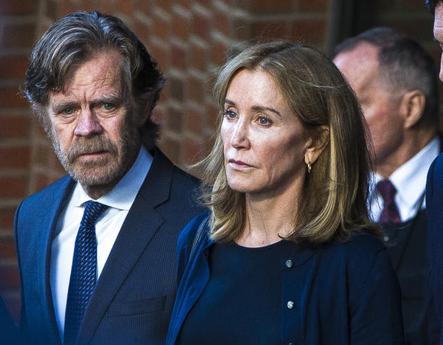 Felicity Huffman, right, and her husband, William H. Macy, walk out of the John Joseph Moakley United States Courthouse in Boston on Sep. 13, 2019. (Photo by Nic Antaya for The Boston Globe via Getty Images)