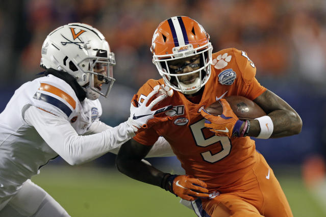 Clemson wide receiver Tee Higgins (5) runs for a touchdown while Virginia cornerback Nick Grant (1) misses the tackle duriung the first half of the Atlantic Coast Conference championship NCAA college football game in Charlotte, N.C., Saturday, Dec. 7, 2019. (AP Photo/Gerry Broome)