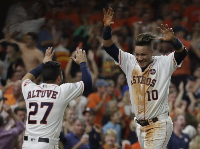 Houston Astros' Yuli Gurriel is congratulated by Jose Altuve after scoring during the fifth inning of Game 7 of baseball's American League Championship Series against the New York Yankees Saturday, Oct. 21, 2017, in Houston. (AP)