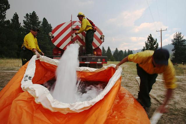 Members of the Mountain Home Fire Department fill a water reservoir called a pumpkin, with 1,800 gallons of water on Monday, Aug. 12, 2013, as they prepare to defend homes from the more than 80,000-acre Elk Complex Fire burning near Pine, Idaho. The Elk Complex remains the nation's No. 1 wildfire fighting priority, since Pine and the neighboring mountain hamlet of Featherville, 8 miles from the flames, remain threatened. (AP Photo/Times-News, Ashley Smith) MANDATORY CREDIT