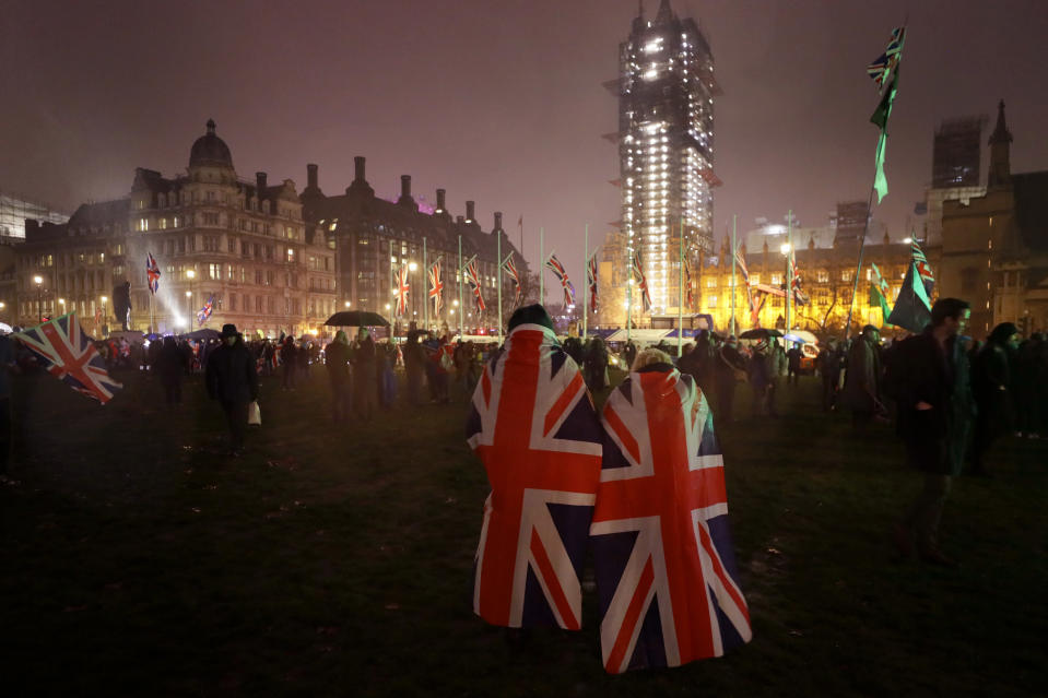 FILE - In this Jan. 31, 2020 file photo, People draped in UK flags walks across Parliament Square during a rainfall in London. Britain and the European Union have struck a provisional free-trade agreement that should avert New Year's chaos for cross-border commerce and bring a measure of certainty to businesses after years of Brexit turmoil. The breakthrough on Thursday, Dec. 24, 2020 came after months of tense and often testy negotiations that whittled differences down to three key issues: fair-competition rules, mechanisms for resolving future disputes and fishing rights. (AP Photo/Kirsty Wigglesworth, File)