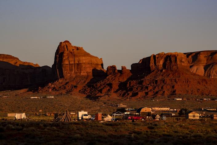 Dawn breaks over homes and sandstone formations near the Monument Valley Navajo Tribal Park