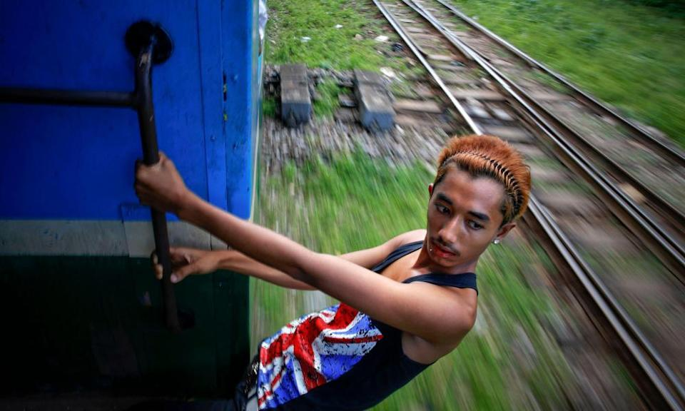 A young man hangs from a moving train in Yangon's suburbs.
