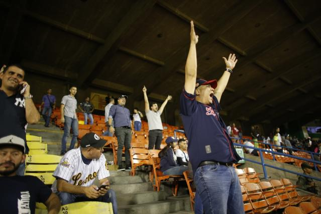 A fan of Leones de Caracas screams during the opening winter league baseball game against Tigres de Aragua in Caracas, Venezuela, Tuesday, Nov. 5, 2019. Venezuela's beloved Winter League baseball season opened Tuesday with hundreds of cheering fans converging on the stadium in Caracas and elsewhere throughout the crisis-torn South American nation. (AP Photo/Ariana Cubillos)