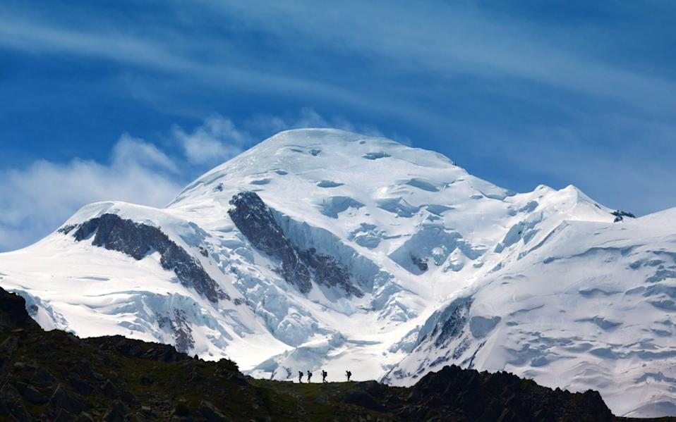 Hikers on a ridge with Mt Blanc in the background - Getty