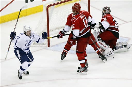 Tampa Bay Lightning's Steven Stamkos (91) celebrates after he scored the game-winning goal against the Carolina Hurricanes' Tim Gleason (6), Cam Ward (30) and Eric Staal (12) during the overtime period of an NHL game in Raleigh, N.C. on Saturday, March 3,  2012.  Tampa Bay won 3-2. (AP Photo/The News & Observer, Chris Seward) MANDATORY CREDIT