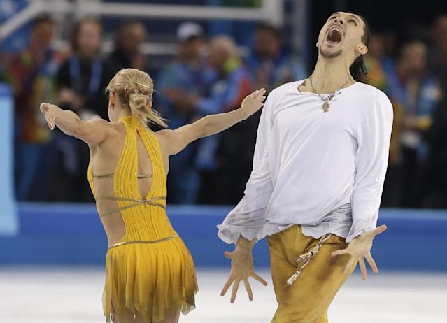 Tatiana Volosozhar and Maxim Trankov of Russia react after their routine in the pairs free skate figure skating competition at the Iceberg Skating Palace during the 2014 Winter Olympics, Wednesday, Feb. 12, 2014, in Sochi, Russia. (AP Photo/Darron Cummings)